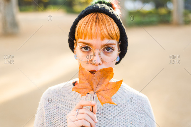Cute millennial holding a leaf in nature