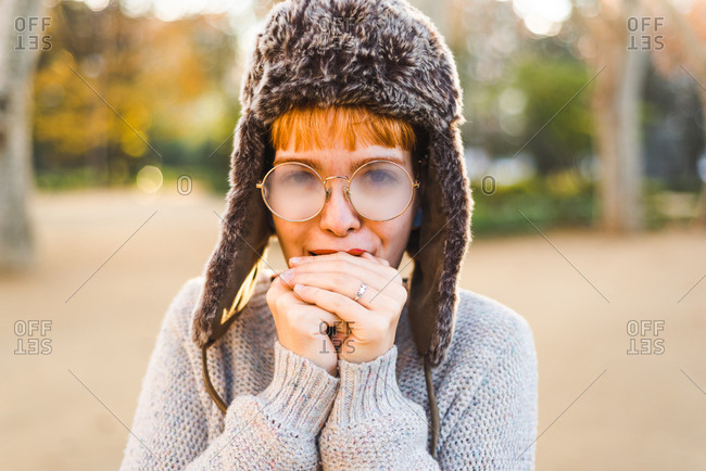 Woman warming her hands with steamed glasses