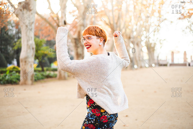 Cute trendy woman dancing in a park