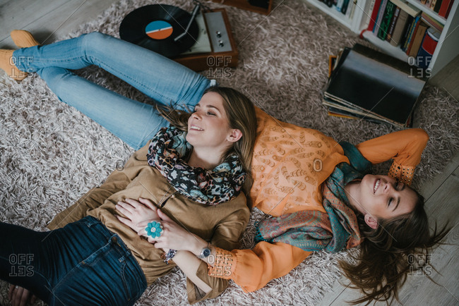 Twin sisters enjoying and smiling together, while lying down on the floor at home