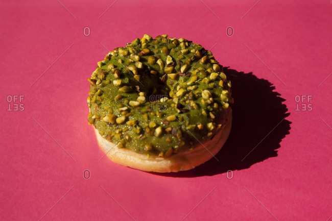 One donut coated with a green sugar with nuts on pink background