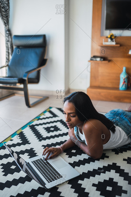 Beautiful African American female in stylish outfit browsing laptop while lying on ornamental carpet in cozy room