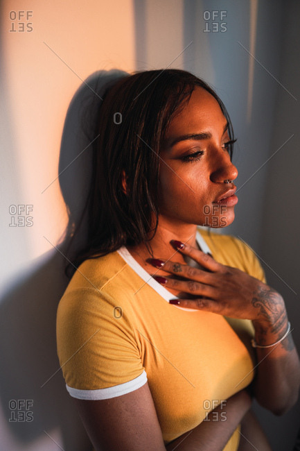 Unhappy African American woman touching neck and embracing herself while sitting near wall at home