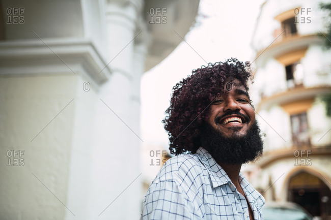 Side view happy young Hispanic man in shirt looking at camera near column on street in Colonial Zone in Santo Domingo city, Dominican Republic