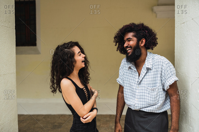 Happy young Hispanic man and woman in casual wear near columns on street in Colonial Zone in Santo Domingo city, Dominican Republic
