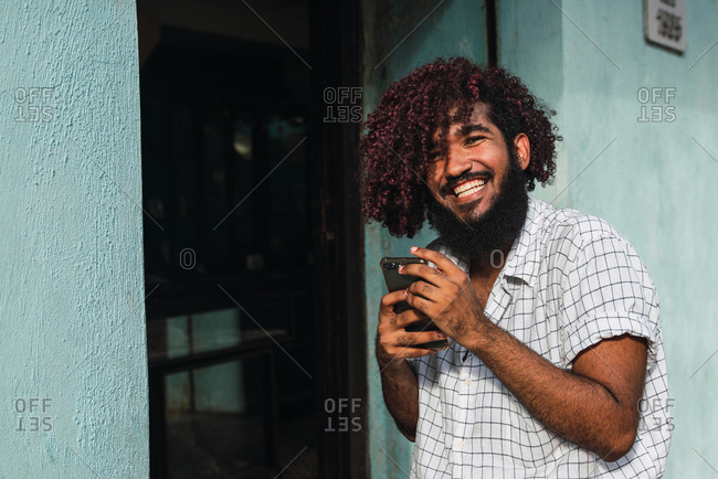 Young smiling Hispanic man in shirt with mobile phone near door and blue wall on street in Colonial Zone in Santo Domingo city, Dominican Republic