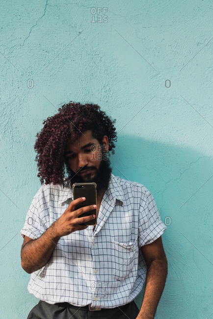 Young Hispanic man in shirt with hand in pocket browsing in mobile phone near blue wall on street in Colonial Zone in Santo Domingo city, Dominican Republic
