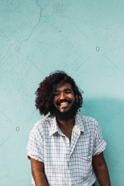 Young smiling Hispanic man in shirt near blue wall on street in Colonial Zone in Santo Domingo city, Dominican Republic