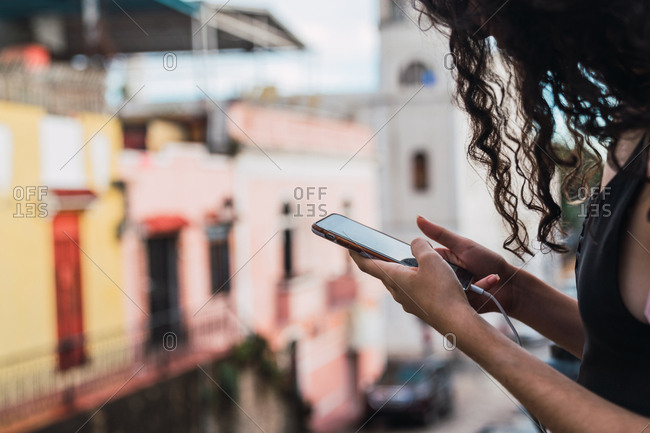 Unrecognizable female with curly hair browsing modern smartphone while standing on blurred background of street in Colonial Zone of Santo Domingo