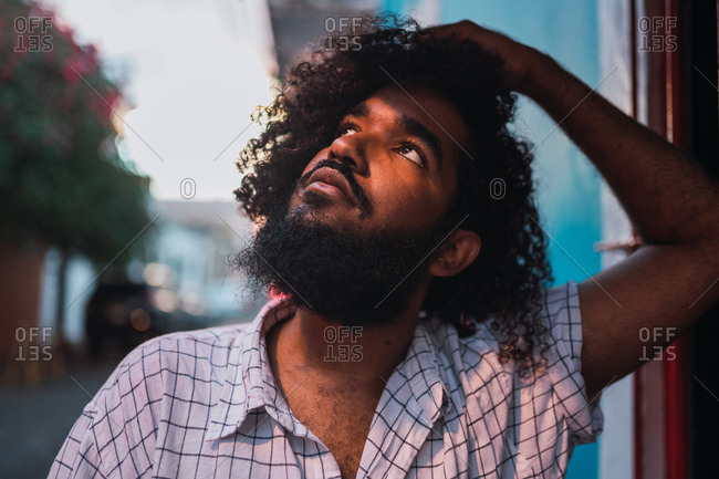Young Hispanic guy in casual wear with curly hairs and hand on head looking away and leaning on building on street in Colonial Zone in Santo Domingo city, Dominican Republic