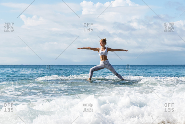 Blonde woman practicing yoga on a rock in the middle of the ocean in Uluwatu, Bali