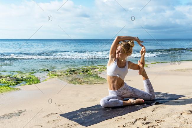 Blonde woman practicing yoga at the beach in Uluwatu, Bali