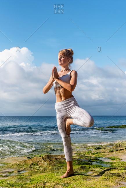 Blonde woman practicing yoga on a rocky beach in Uluwatu, Bali