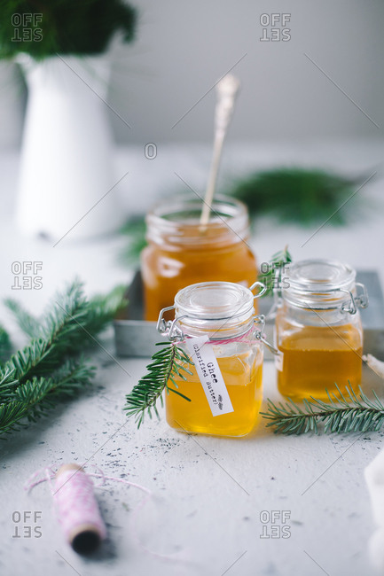 Jars filled with freshly made ghee garnished with pine needles