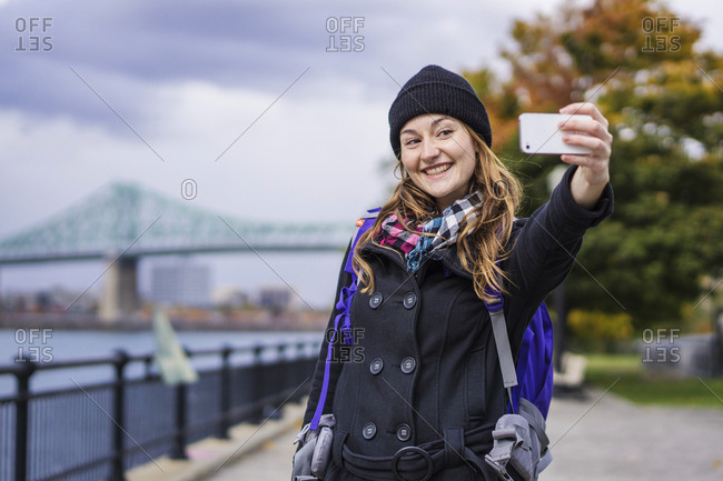 Solo woman traveller using smartphone to take selfie, Montreal, Quebec, Canada