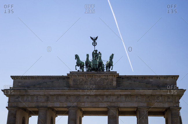 An aircraft flies far above the Brandenburg Gate in Berlin, Germany.