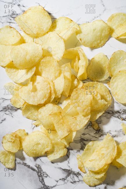 Close up image of potato crisps on marble surface