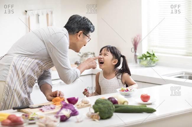 Happy little Chinese girl and grandfather cooking in kitchen