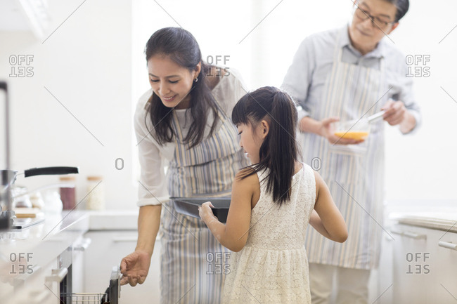 Happy little Chinese girl and grandparents baking cookies in kitchen