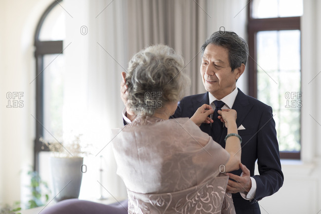 Senior Chinese wife adjusting tie for her husband