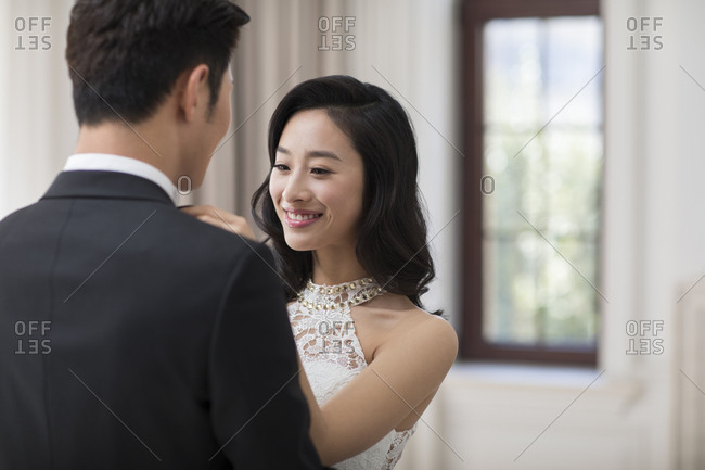Young Chinese wife adjusting bow tie for her husband