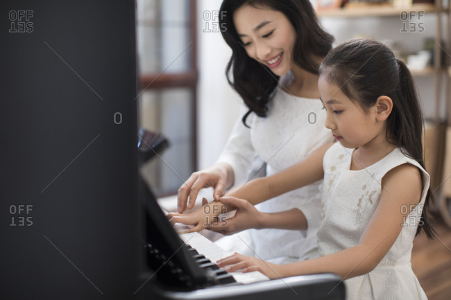 Chinese mother teaching daughter to play the piano