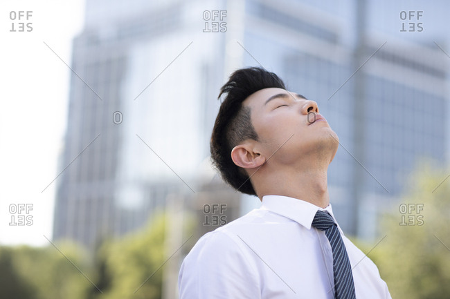 Young Chinese businessman relaxing with head cocked