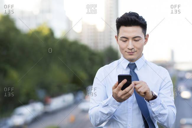 Confident young Chinese businessman using smart phone
