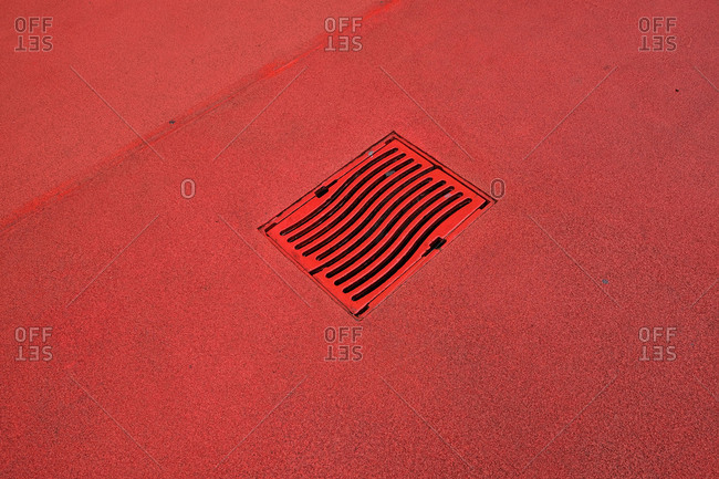 Looking down on a red sidewalk in red light