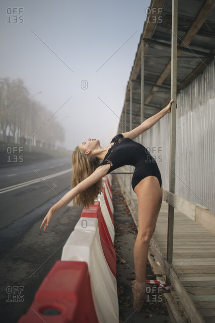 Side view of ballerina wearing black leotard stretching at sidewalk in city