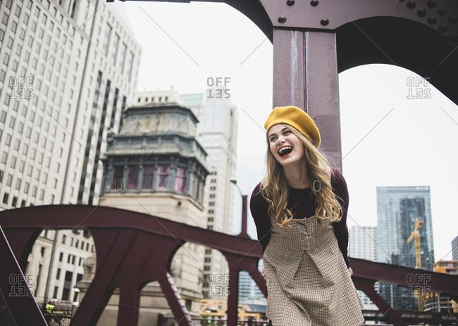 Cheerful teenage girl standing on bridge against buildings in city