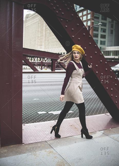 Full length of fashionable teenage girl walking at sidewalk in city