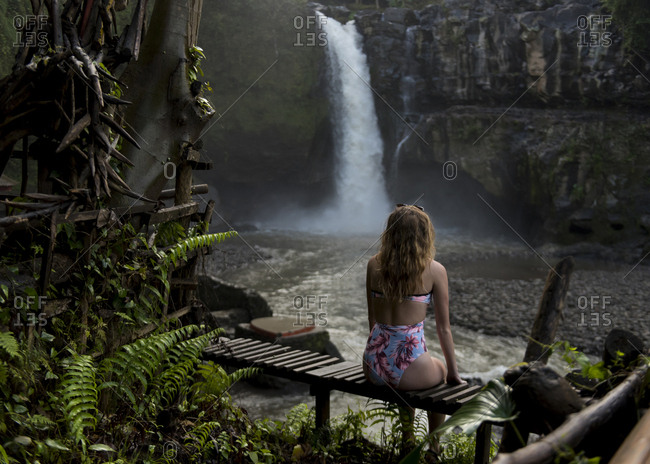 Rear view of female tourist wearing swimsuit looking at waterfall in forest