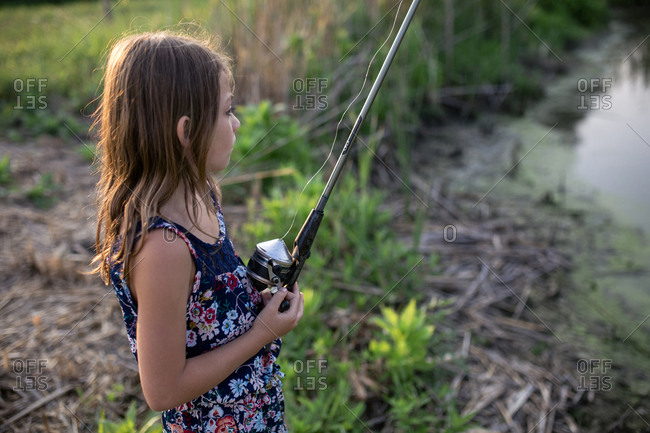 Side view of thoughtful girl holding fishing rod while standing on field