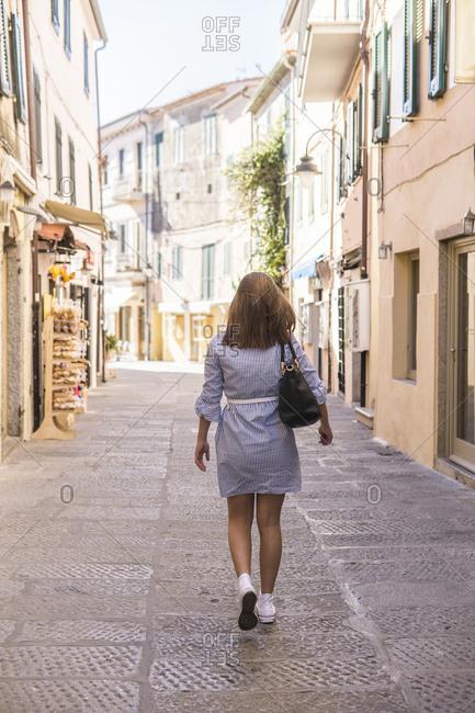 Rear view of teenage girl walking on alley amidst buildings