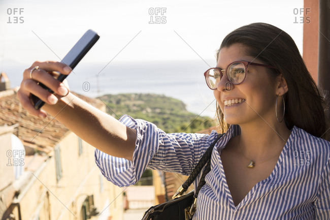 Close-up of smiling female teenager taking selfie