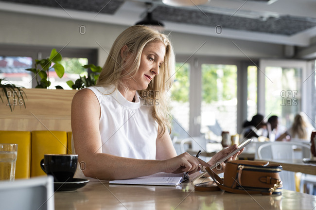Confident woman with diary using tablet computer at table in cafeteria