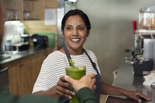 Female owner giving drink to customer in cafeteria