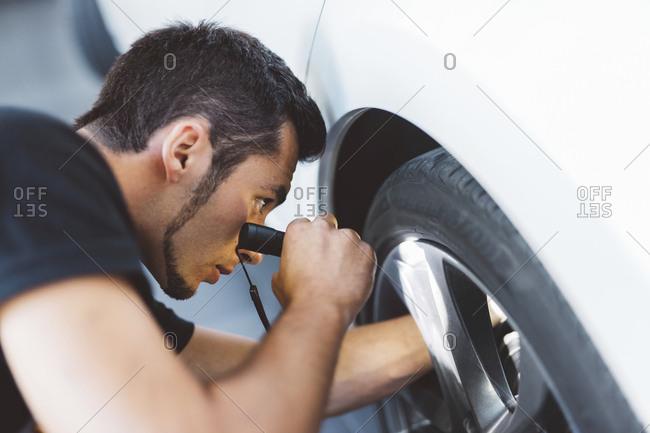 Mechanic holding illuminated flash light while fixing car tier