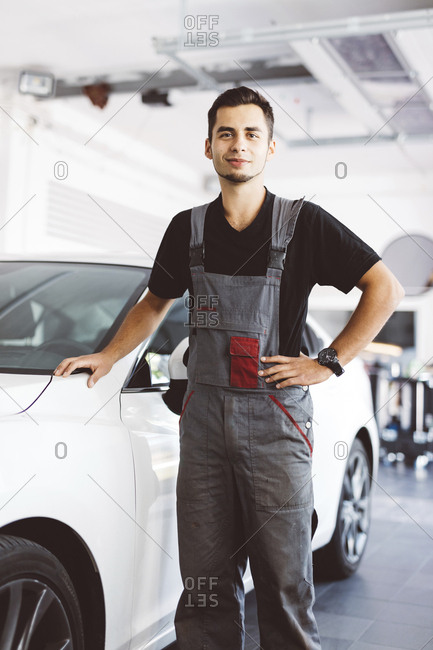 Portrait of confident engineer standing by car in auto repair shop