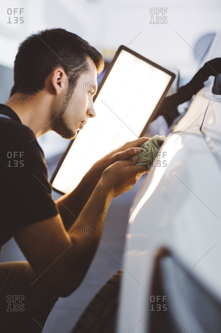 Engineer rubbing car with napkin by illuminated lamp while working in auto repair shop
