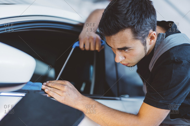 Engineer repairing car window at auto repair shop