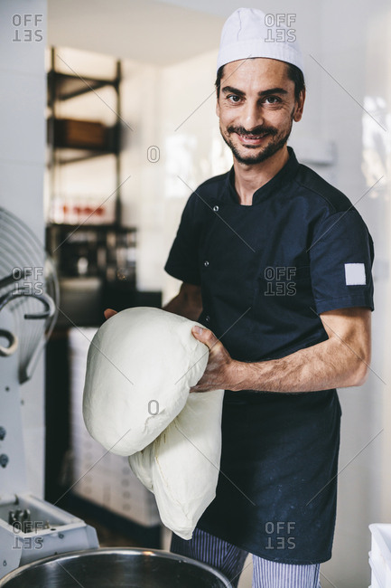 Portrait of smiling chef holding dough in commercial kitchen at pizzeria