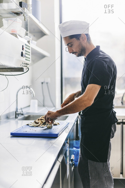 Side view of chef cutting mushrooms in commercial kitchen at pizzeria