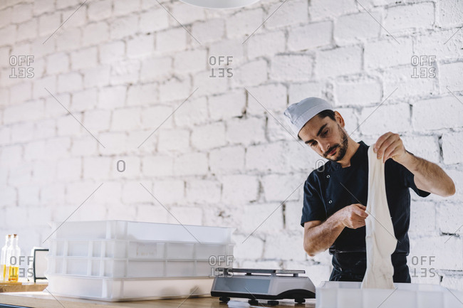 Chef holding dough while standing against wall in commercial kitchen at pizzeria