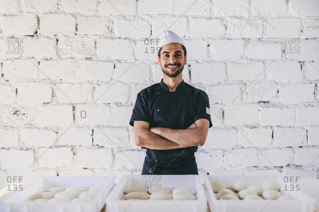 Portrait of confident smiling chef with arms crossed standing by dough in containers against wall at pizzeria