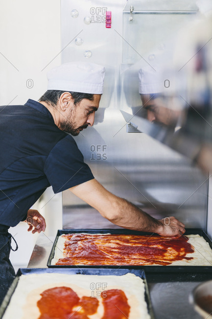 Side view of chef applying pizza sauce on dough in baking sheet at commercial kitchen