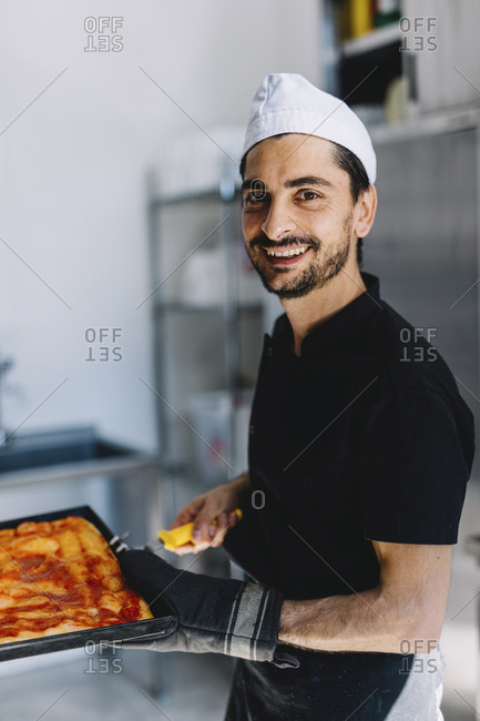 Portrait of smiling chef holding dough with pizza sauce on baking sheet in commercial kitchen at pizzeria