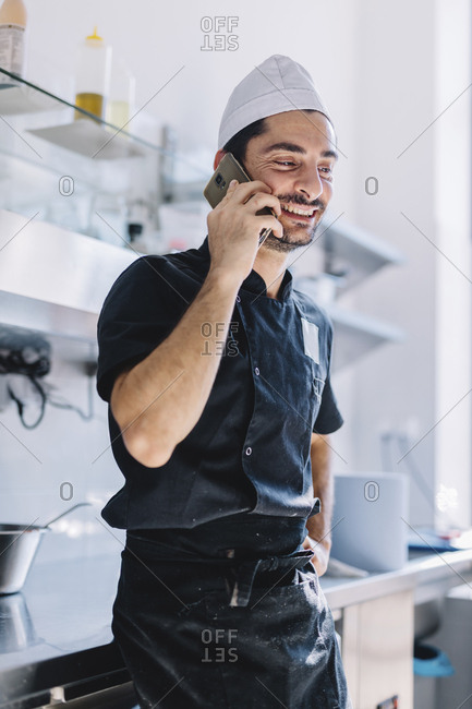 Smiling chef talking on smart phone while standing in commercial kitchen at pizzeria