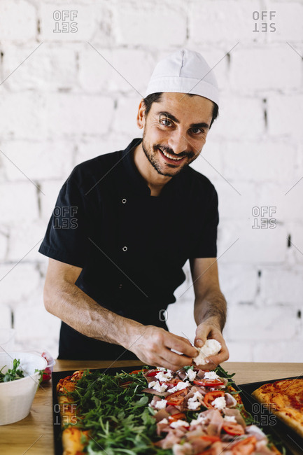 Portrait of smiling chef putting cheese on raw pizza in commercial kitchen at pizzeria